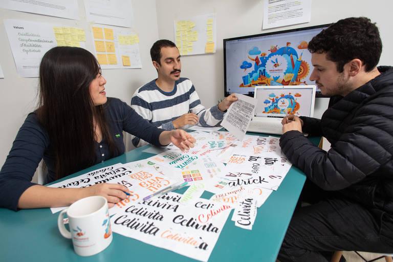 Os designers e sócios Cindy Nakashima, Thiago Reginato (à esq.)  e Bruno Scodeler em reunião do Estúdio Maquinário, agência que cria identidades visuais