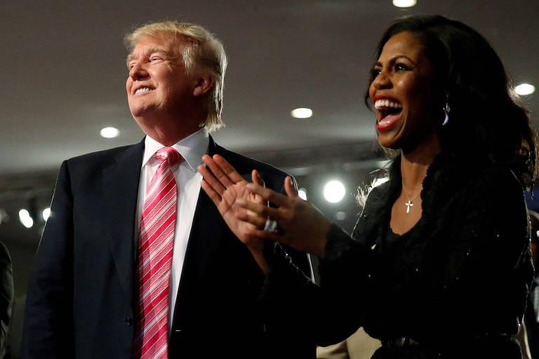 Vestido com terno preto com paletó aberto, camisa branca e gravata vermelha com listras brancas, Trump sorri olhando de lado. À sua direita está Omarosa, que usa um vestido preto sorri e bate palmas.