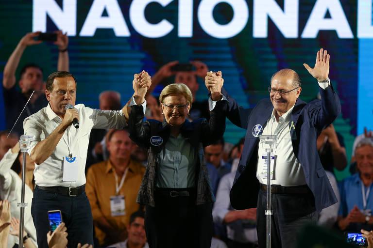 Doria, a vice de Alckmin, Ana Amélia, e Geraldo Alckmin na convenção nacional do PSDB, em Brasília. Os três dão as mãos, com os braços erguidos