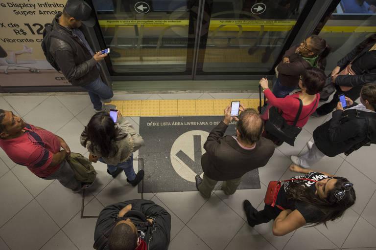 Pessoas usam celular no metrô de São Paulo; 31% dos brasileiros entrevistados dizem não se importar com a coleta de dados