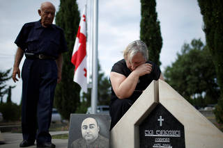 Dali Baramidze, 71, cries over the tombstone of her son Leri Lagurashvili on the 10th anniversary of Georgian-Russian war at the memorial cemetery of the Georgian soldiers killed during the war in Tbilisi