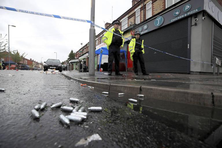 Policiais em rua onde há balas no chão