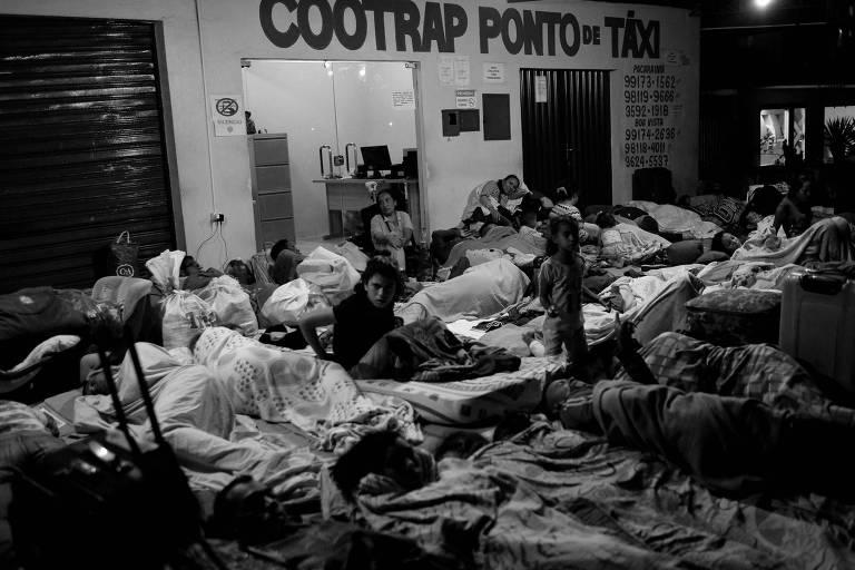 Pessoas deitadas em um salão, todas com cobertores