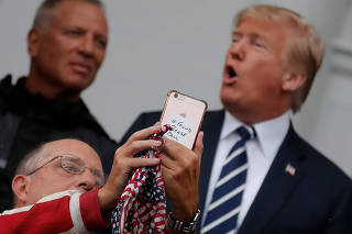A supporter takes a selfie with U.S. President Donald Trump as he meets with supporters from a group called
