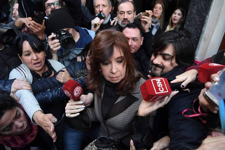 Cristina Kirchner olha para baixo enquanto é rodeada por jornalistas com microfones