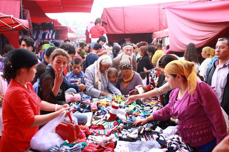 Pessoas escolhem produtos em mercado de rua