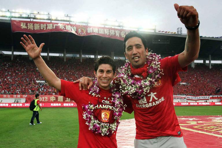 Lucas Barrios (à dir.) e Dario Conca celebram vitória do Guangzhou Evergrande no campeonato chinês