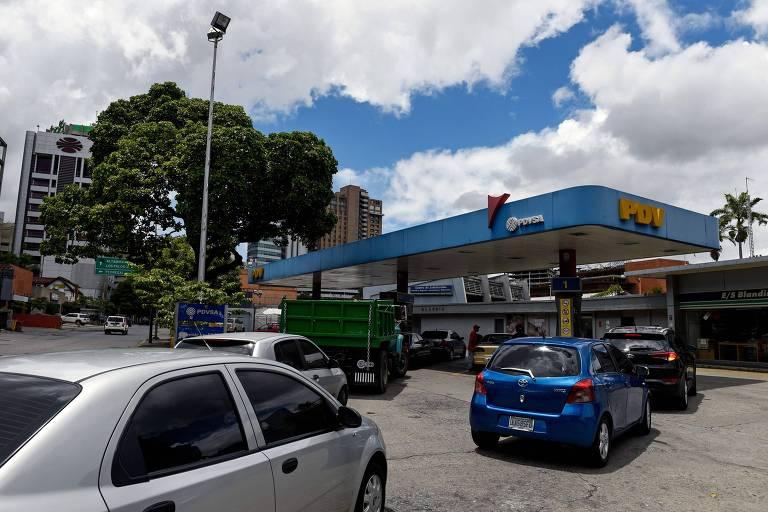 Três carros fazem fila para entrar na bomba de um posto de gasolina.
