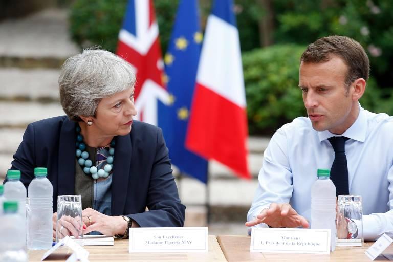 Macron aparece à direita com camisa social azul clara e gravata preta, enquanto May está à esquerda com blazer preto e camisa estampada verde, branca e marrom.  Os dois estão sentados à mesa com garrafas d'água uma em frente ao outro. Ao fundo, as bandeiras do Reino Unido, da União Europeia e da França aparecem em um mastro.