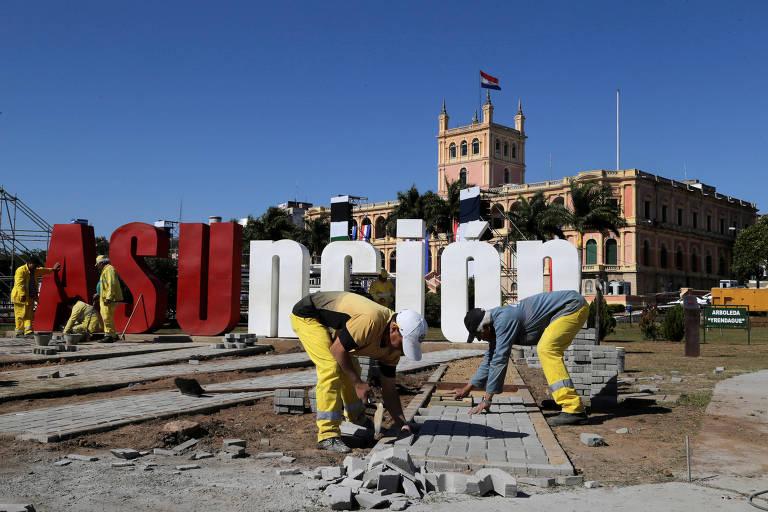 Operários assentam pedras em uma área de praça. Ao fundo, está um banner de letras em tamanho gigante da palavra Asunción, com ASU em maiúsculo e vermelho e as demais letras em minúsculo e branco. Em terceiro plano, o Palácio dos López.