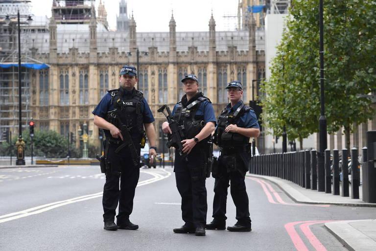 Três policiais armados olham na mesma direção, com o Parlamento ao fundo