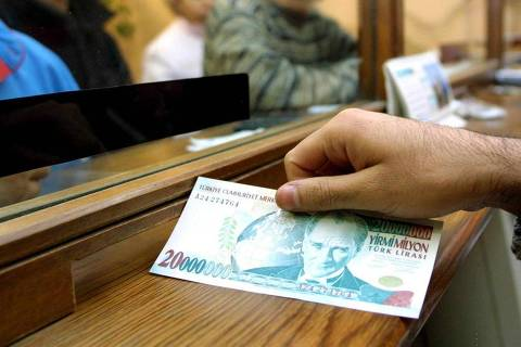 ORG XMIT: 271401_1.tif Nota de 20 milhões de liras turcas que entrou em circulação na Turquia devido à inflação. (A cashier gives a new 20 million banknote to an unidentified customer in Istanbul, Turkey, 05 November 2001. Turkey introduced 05 November banknotes worth 20 million lira (12.8 USD, 14,27 Euro), the result of chronic inflation plaguing the country for the past several decades. The previous biggest note, worth 10 million Turkish lira, had entered circulation in November 1999.) AFP PHOTO/KERIM OKTEN