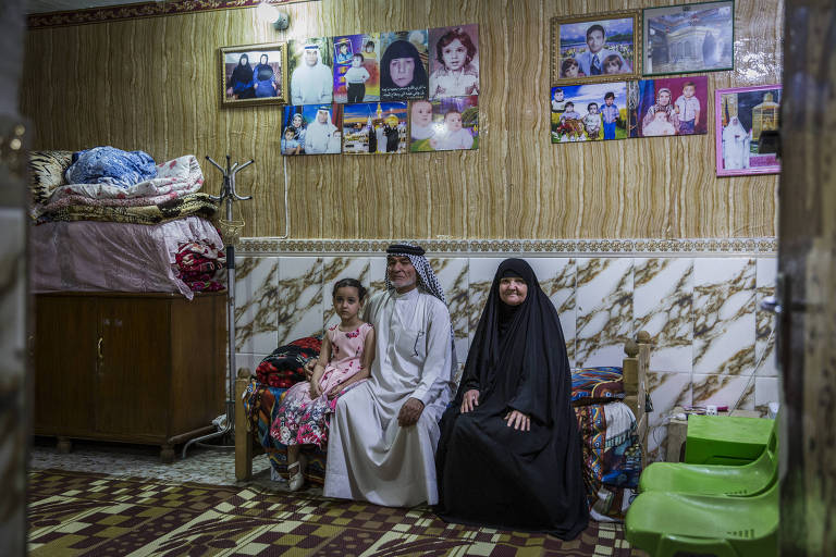 Capt. Harith al-Sudani?s father, Abid al-Sudani, center, with his wife, Laisa Hashim Shuaith, and one of Captain Sudani?s daughters at their home in Baghdad, May 8, 2018. Capt. Harith al-Sudan, who was believed to be executed by the Islamic State, posed as a militant jihadist while passing critical information to a secret branch of Iraq?s national intelligence agency. (Ivor Prickett/The New York Times)