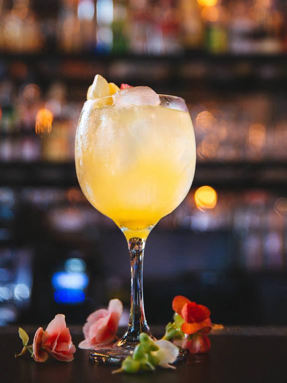 Trabuca Bar - Drinque Flower Power (gim, água de flor de laranjeira, ameixa japonesa, flor de sabugueiro, água tônica, acompanhado de uma flor comestível (de sabor ácido)