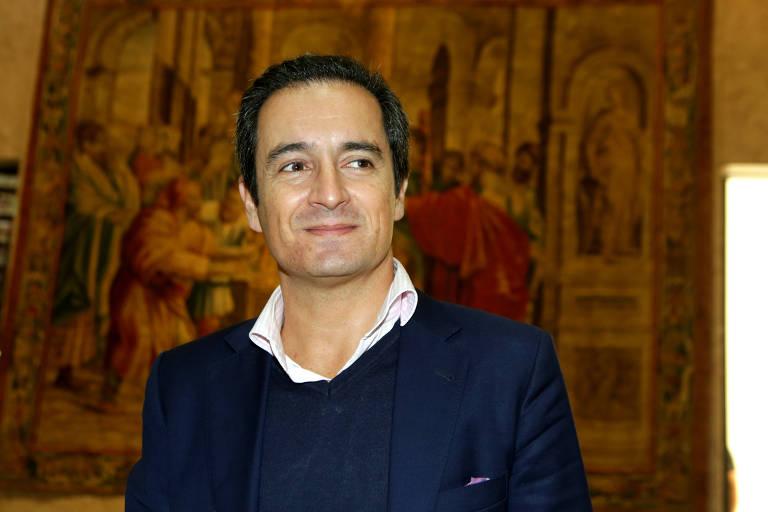 Retrato de meio corpo de Paulo Lourenço, de suéter azul e blaser, que sorri e olha lateralmente diante de quadro de arte sacra em ambiente interno