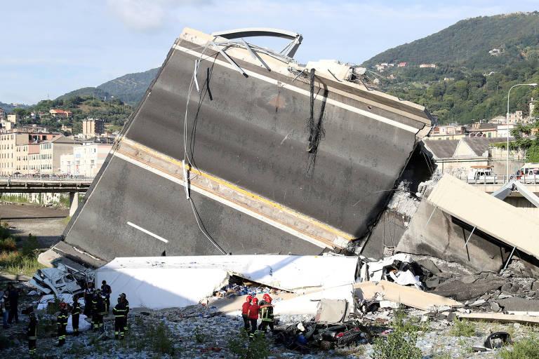 Socorristas e bombeiros aparecem na parte de baixo da imagem, ocultos na sombra de um dos pedaços da ponte que caiu
