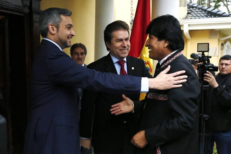 Observado por Castiglioni, Abdo coloca a mão no ombro de Evo, enquanto este estende a mão para o colega paraguaio