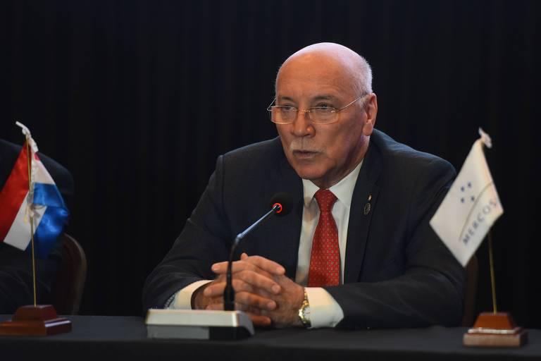Loizaga aparece sentado, falando diante de um microfone, entre duas pequenas bandeiras do Paraguai e do Mercosul na mesa. Ele veste terno preto, camisa branca e gravata vermelha.