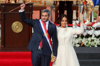Paraguay's new President Mario Abdo Benitez gestures to the audience alongside Paraguay's First Lady Silvana Lopez Moreira after being sworn in at the Lopez Palace in Asuncion