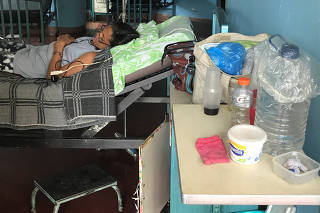 Containers filled with water are seen next to the bed of a patient at the Central University of Venezuela hospital in Caracas