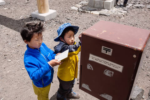 Young hikers drop postcards into a mailbox outside the post office on the summit of Mt. Fuji, in Fujinomiya, Japan, July 24, 2018. Some 300,000 hikers reach the summit of Japan's highest mountain each year, many of whom visit the mountaintop post office. Two or three days a week during the summer hiking season, a weather-beaten tractor trundles up the 2.8 mile trail to collect crates of postcards and letters to bring down. (Ko Sasaki/The New York Times) ORG XMIT: XNYT25 DIREITOS RESERVADOS. NÃO PUBLICAR SEM AUTORIZAÇÃO DO DETENTOR DOS DIREITOS AUTORAIS E DE IMAGEM