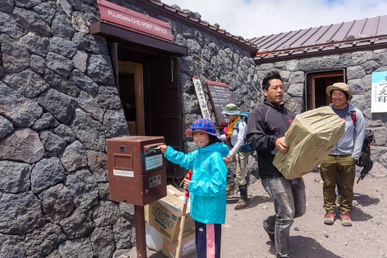 Criança coloca carta em caixa do correio na agência postal no topo do monte Fuji