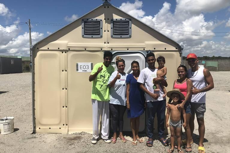 Família de oito venezuelanos, incluindo três crianças, posa diante de uma cabana de plástico em acampamento em Roraima