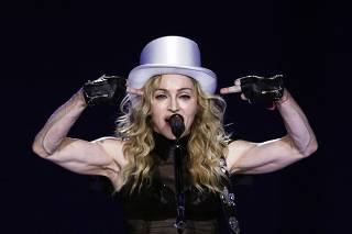 U.S. singer Madonna gestures as she performs during her Sticky and Sweet tour at the O2 Arena in London