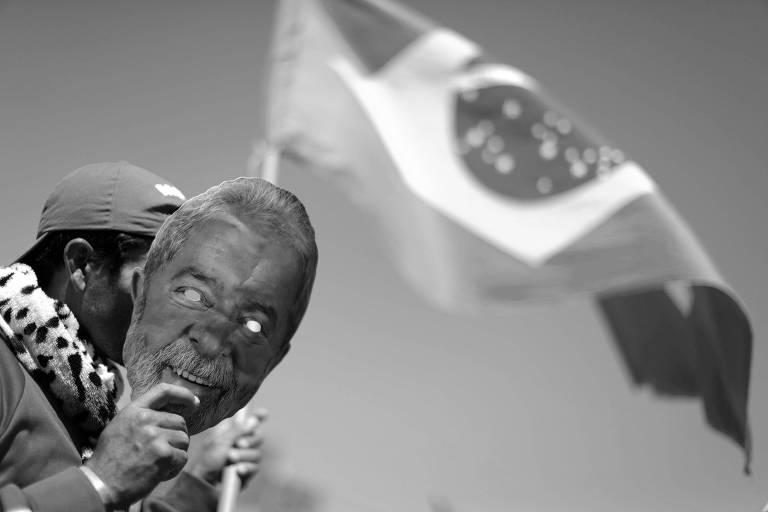 Manifestante pró-Lula segura máscara com o rosto do ex-presidente durante marcha em Brasília