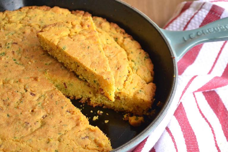 Pão de milho salgado na frigideira em que é preparado. Sua massa é amarelada e a textura lembra um bolo de fubá