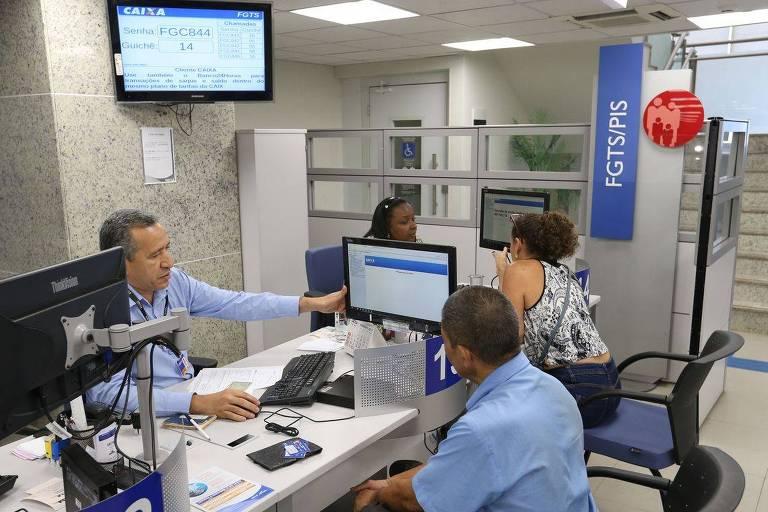 há um homem sentado atrás da mesa, apontando para a tela do computador. Do outro lado da mesa branca, um homem de camisa azul olha para a tela. Ao fundo, lê-se a placa FGTS