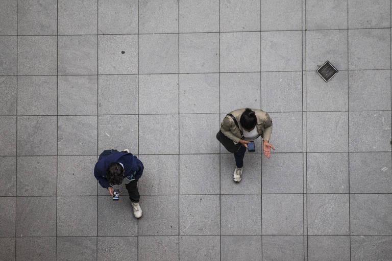 Pessoas caminham enquanto olham celulares; envio de emails registrou recorde em 2018