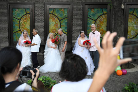 Participants pose at a photo shoot event organized to recreate wedding photos for elderly couples, who have been married for more than 50 years, a day ahead of the Qixi festival, also known as Chinese Valentine's Day, in Tianjin, China August 16, 2018. REUTERS/Tingshu Wang?      TPX IMAGES OF THE DAY ORG XMIT: PEK03