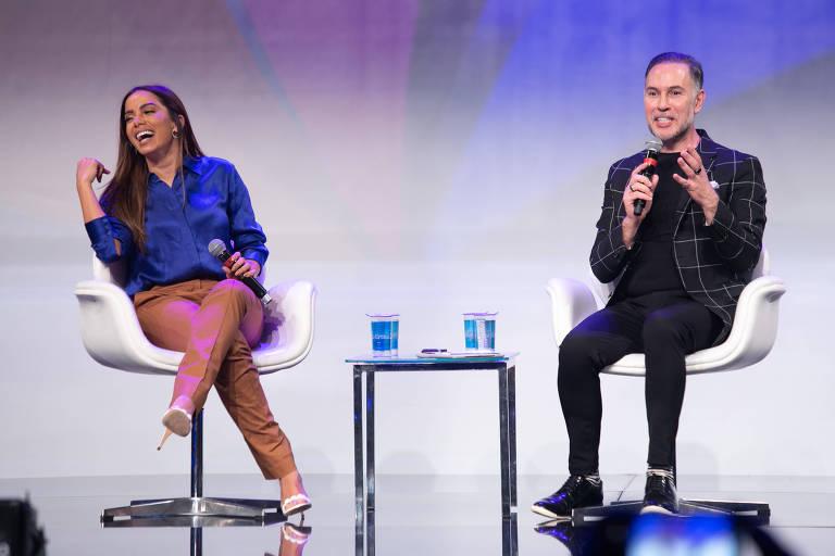 A cantora Anitta no palco, sentada, ao lado do moderador Ricardo Mota
