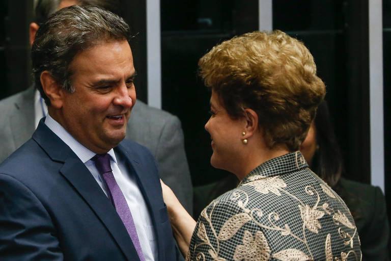 Aécio Neves, de frente, vestindo terno azul, cumprimenta a ex-presidente Dilma, que é vista de costas, usando um terno floral verde.