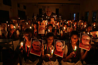 Schoolgirls hold candles and photographs of India's former prime minister Atal Bihari Vajpayee to pay him homage during a prayer ceremony inside a school in Chennai