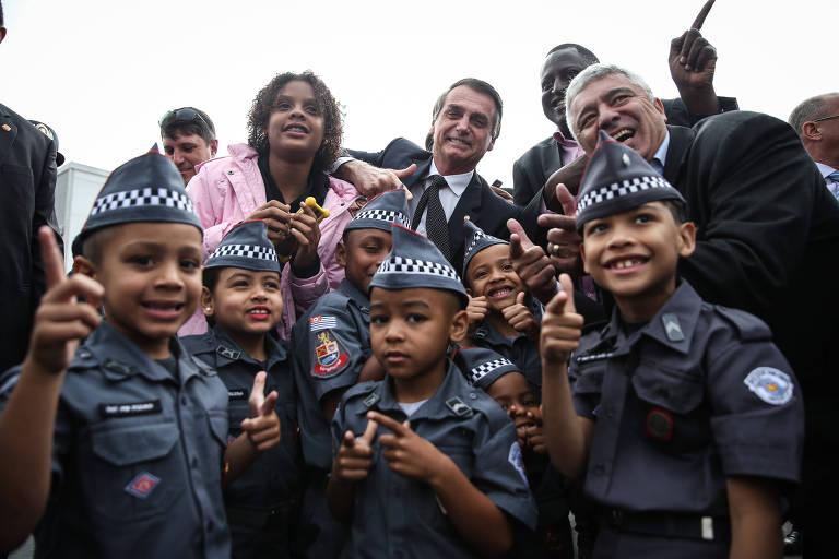 Bolsonaro vestindo terno escuro com camisa branca é cercado por seis crianças, vestidas de PM e fazendo gesto que imita  um revólver.