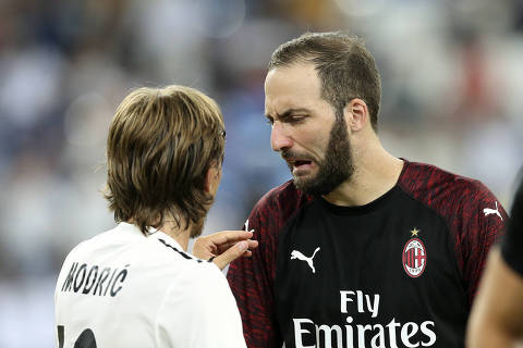 AC Milan's Argentine Gonzalo Higuain, right, talks with Real Madrid's Luka Modric after the Santiago Bernabeu trophy soccer match between Real Madrid and AC Milan at the Santiago Bernabeu stadium, in Madrid, Saturday, Aug. 11, 2018. (AP Photo/Andrea Comas) ORG XMIT: AC116
