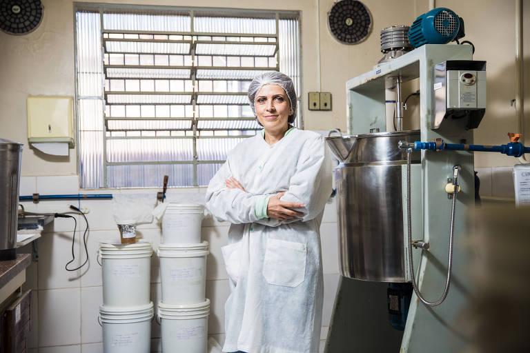 A farmacêutica Cláudia de Araújo Carvalho, 50, na área de produção de sua empresa de cosméticos, com indumentária composta por avental e touca