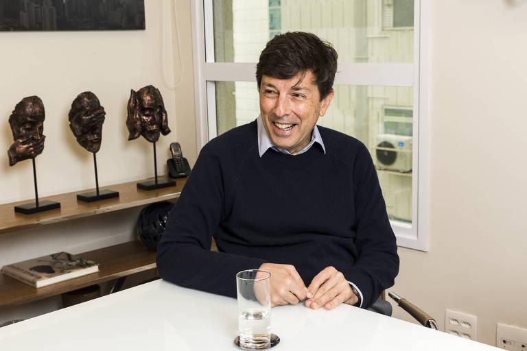 João Amoedo sorri sentado à mesa de uma sala de escritório