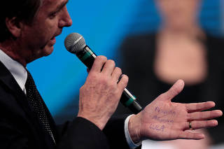 Handwritten notes are seen on the hand of presidential candidate Jair Bolsonaro of the Party for Socialism and Liberation (PSL) during a television debate at the Rede TV studio in Osasco