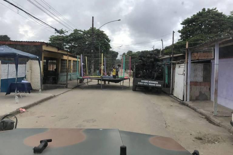 Foto mostra um pula-pula no meio da rua enquanto um tanque com soldados tenta passar