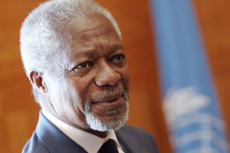 Close de Kofi Annan, de terno cinza, diante da bandeira da ONU
