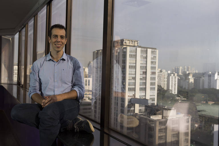 Retrato de Renato Feder, da Multilaser, sentado em frente a uma janela com vista de São Paulo
