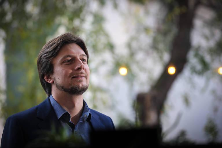 Retrato de Alexandre Guerra, de terno e sem gravata, ao ar livre, olhando para cima