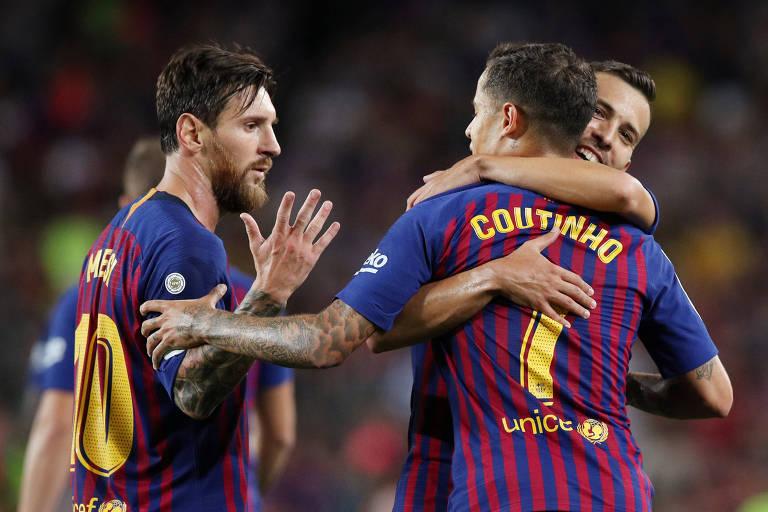 1924554698 Homens com camisa azul e roxa se cumprimentam Messi e Philippe Coutinho  comemoram o segundo gol do Barcelona contra o Alavés ...