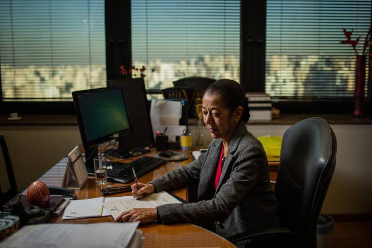 A desembargadora Rilma Aparecida Hemetério em seu gabinete, sentada, fotografada enquanto trabalha
