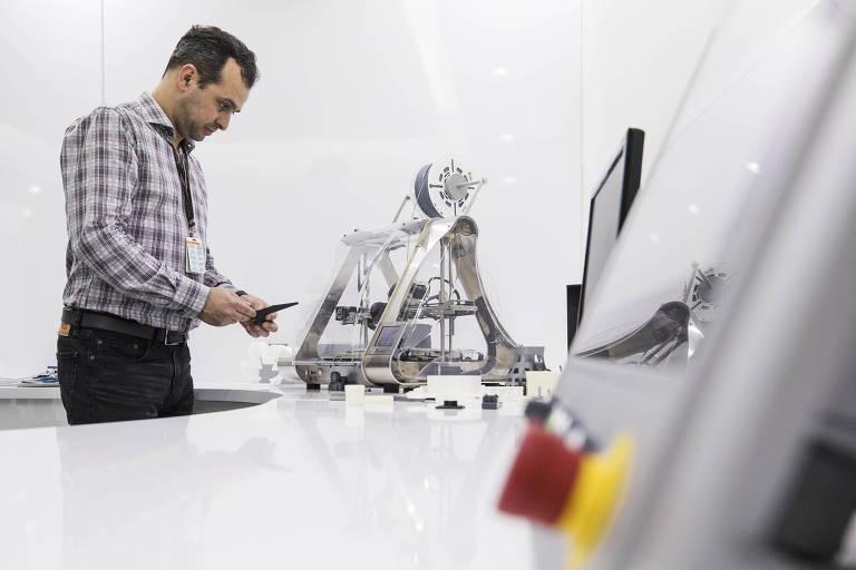 William Franco observa impressora 3D no laboratório de inovação da Natura, em pé, de frente para o objeto