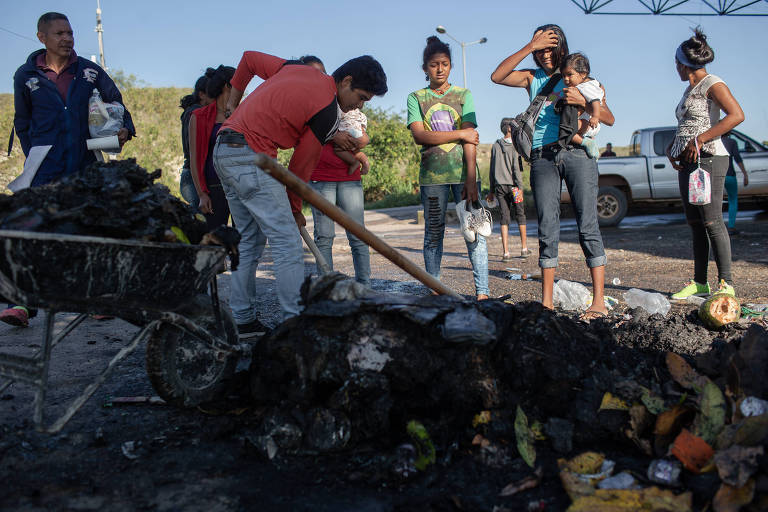 Yineth Manzol (dir., com leço azul na cabeça) e outros venezuelanos observam os restos de suas roupas, alimentos e objetos que foram queimadas por moradores de Pacaraima