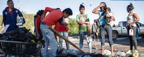 PACARAIMA, RR, BRASIL, 19-08-2018: Venezuelanos observam os restos de suas roupas, alimentos e objetos que foram queimadas por moradores de Pacaraima (RR) durante protesto que expulsou temporariamente os imigrantes venezuelanos. A onda de violência iniciou após um comerciante local ser surrado em uma tentativa de assalto na véspera. Agredidos com pedaços de pau os refugiados foram expulsos das tendas que ocupavam na região da fronteira do Brasil com Venezuela. (Foto: Avener Prado/Folhapress, MUNDO) Código do Fotógrafo: 20516 ***EXCLUSIVO FOLHA***